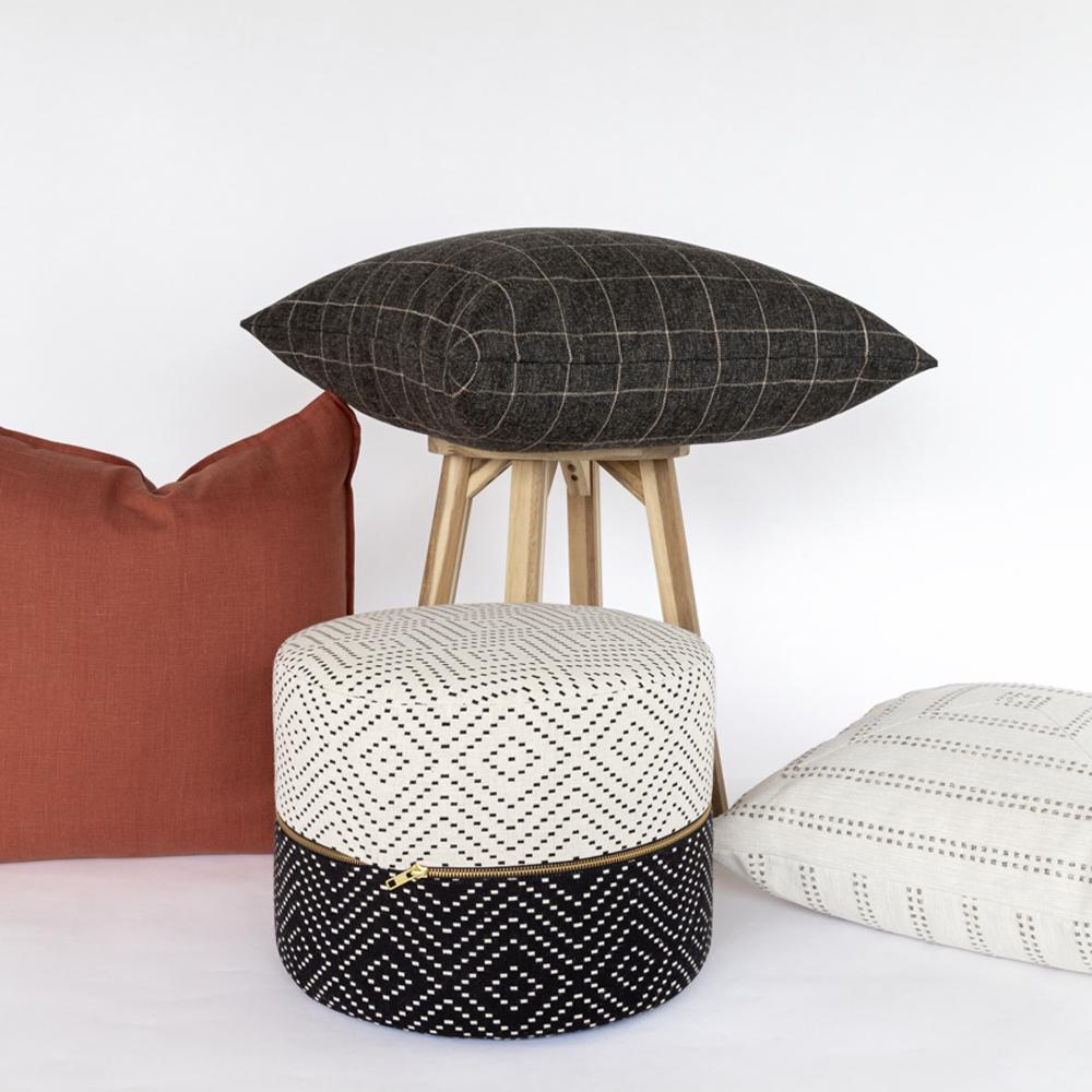 Ava, a black and white diamond pattern mini round ottoman and pillows from Tonic Living