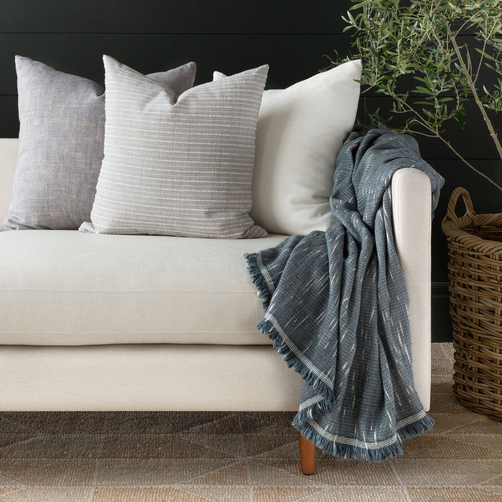 Cream sofa vignette : Misto fog grey stripe pillow combination and Rafael stone blue cotton throw blanket