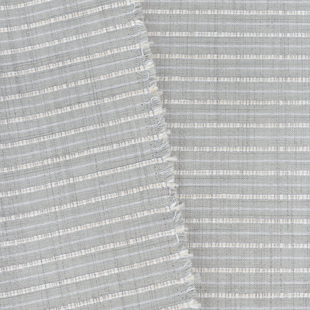 Misto Fog Grey, a cool gray and cream horizontal striped Crypton Home performance fabric: view with selvage edge