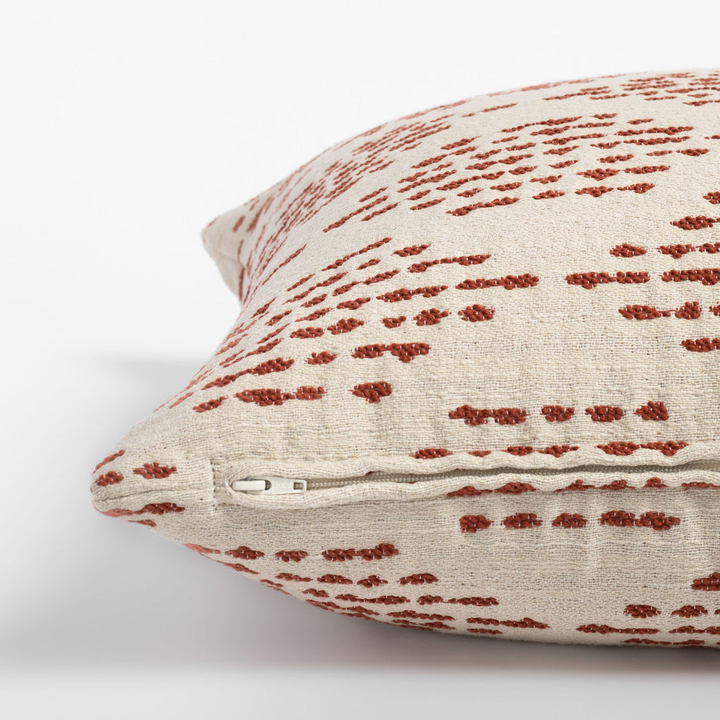 Ophelia Rust, a dotty rust red and cream indoor outdoor pillow : close up zipper view
