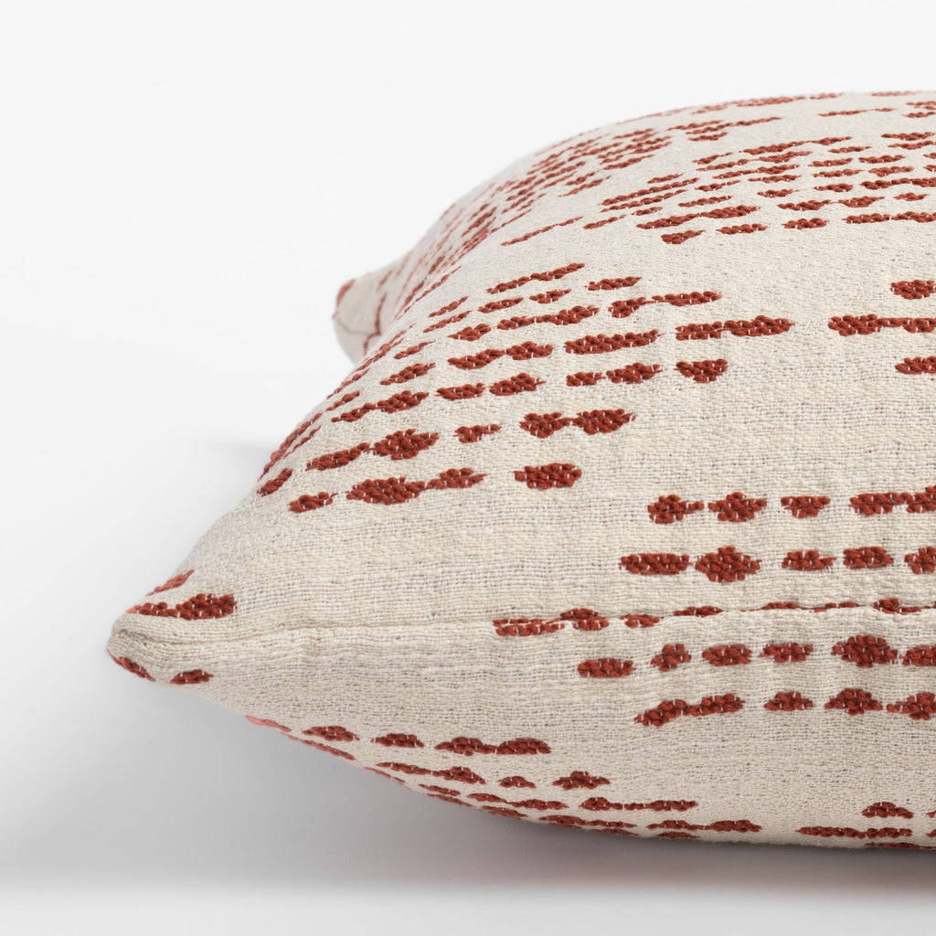 Ophelia Rust, a dotty rust red and cream indoor outdoor pillow : close up side view