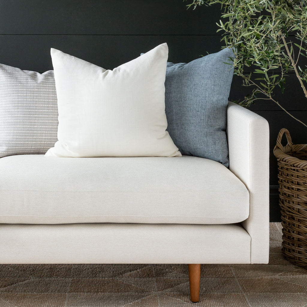 Quinto Vanilla pillow combination with Misto stripe grey and Benton chambray blue pillows on a cream sofa