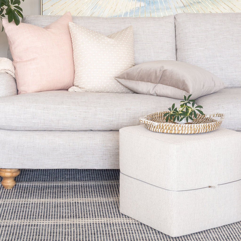 tonic living cream ottoman and beige and pink pillows on a sofa