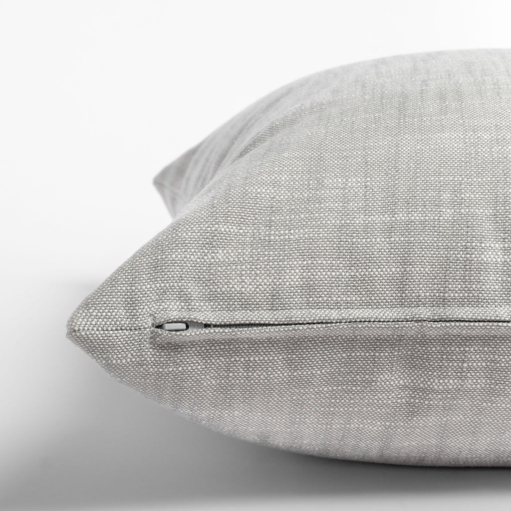 Ryder Zinc, a light gray indoor outdoor pillow: zipper detail