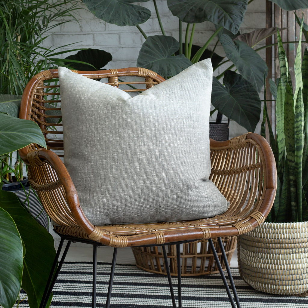 Ryder Zinc light gray pillow on a chair surrounded by plants