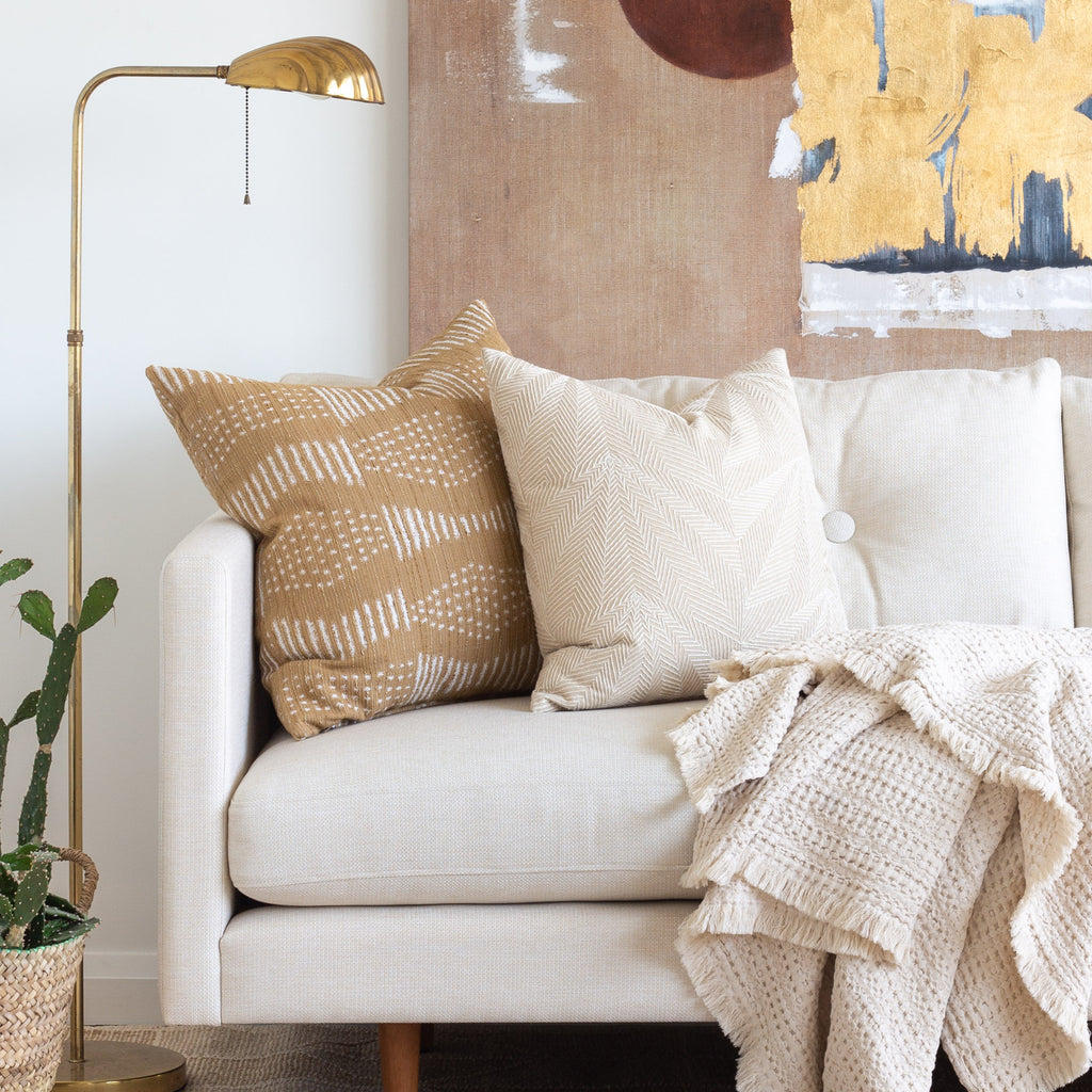 Boho Decor: Sardee beige tonal geometric embroidery pillow and Zipporah cork color pattern pillow on a cream couch