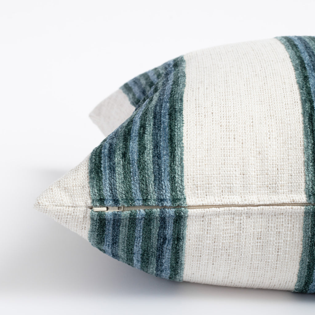 a bold blue green and cream striped pillow with a chenille texture zipper detail