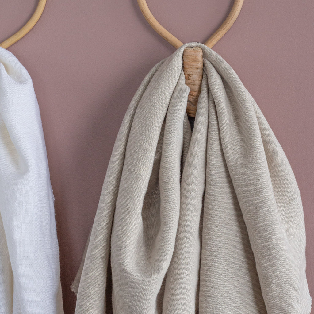 warm neutral beige linen fabric draped on a wall hook
