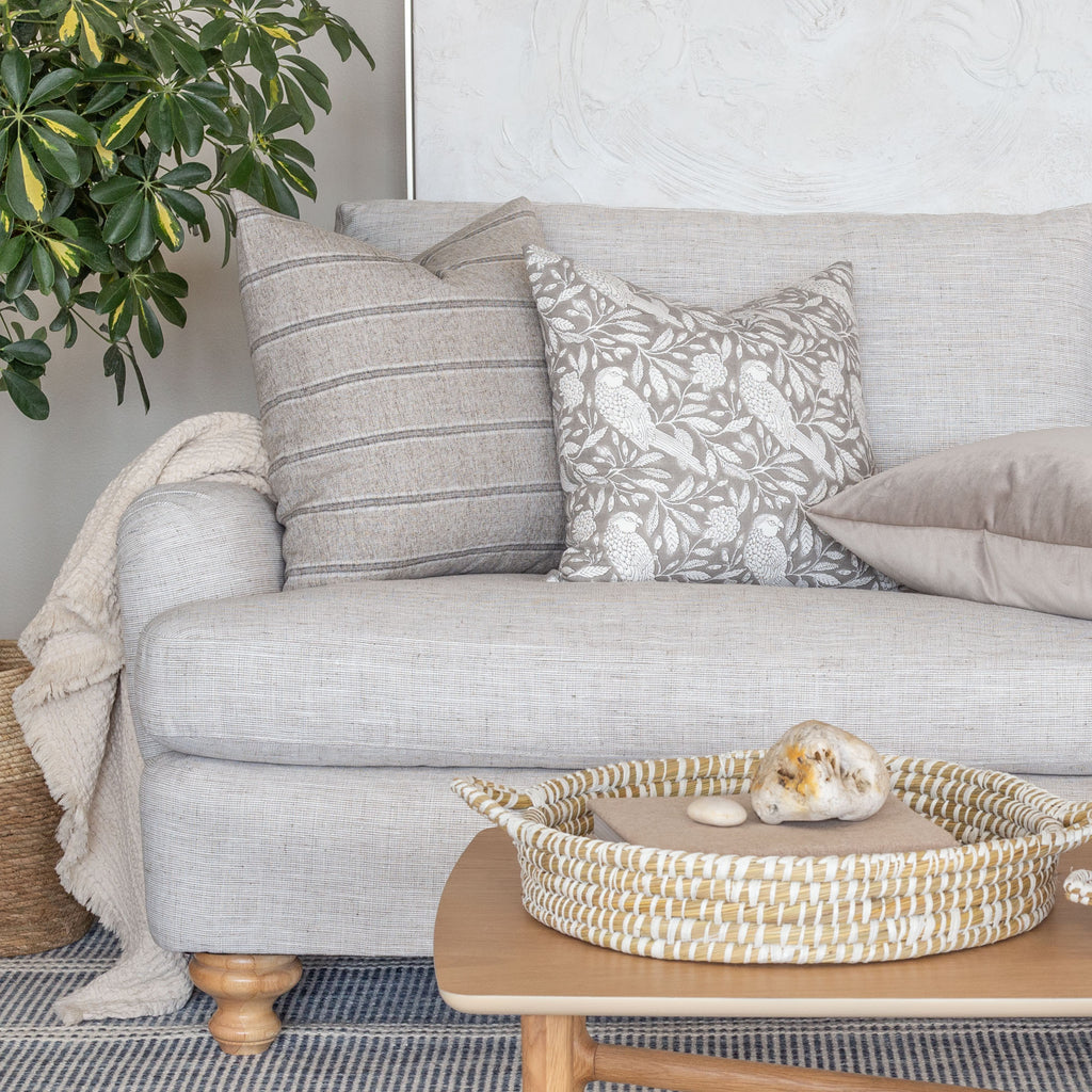 grey stripe and botanical print pillows on beige sofa