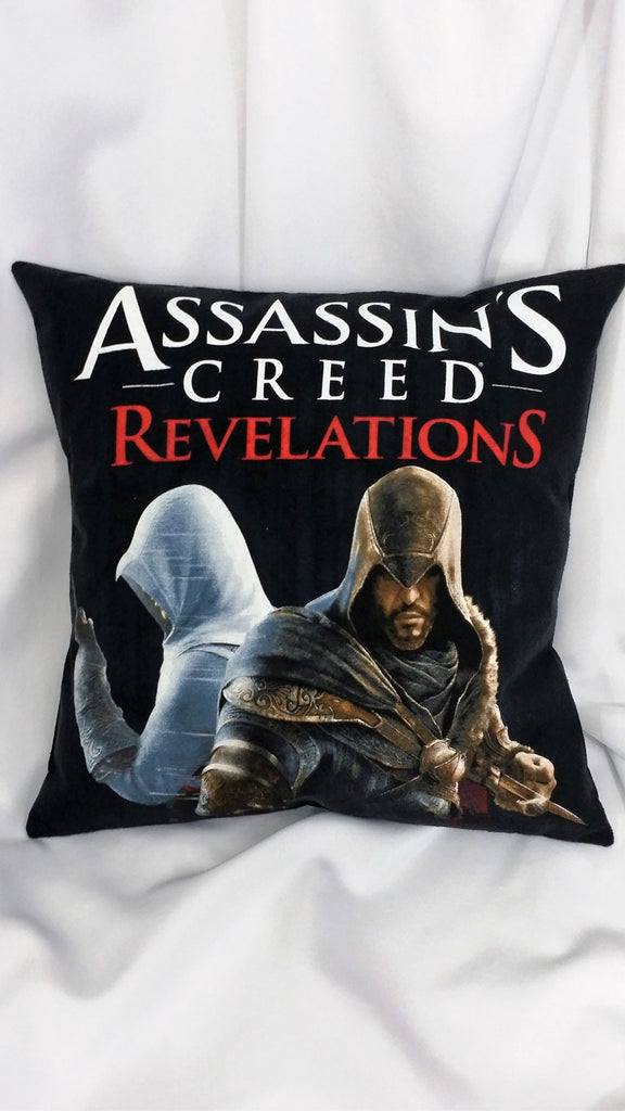 Assassin's Creed Revelations tshirt made into a decorative throw pillow with Ezio Auditore on a black background with an unnamed white cloaked assassin and the Assassin's Creed Revelations logo.