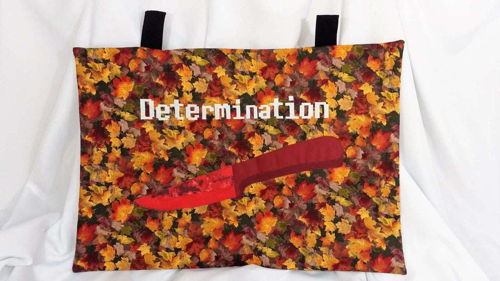 "On one side it features ""Determination"" with a red bloody knife. The other side has a save star and the words, ""Playfully Crinkling"" on a background of fall leaves."
