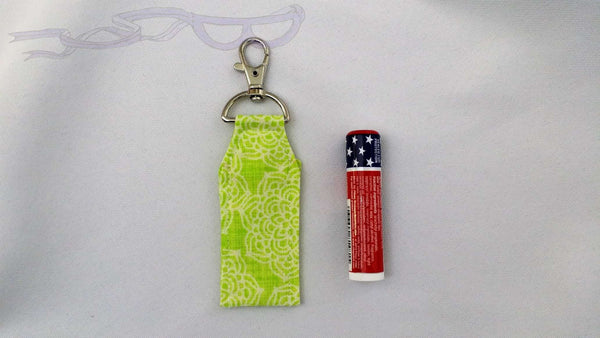 Keep your little necessary items easy to find with this carrying clip. It has white flowers on a lime green background.