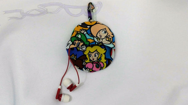 This ear bud pouch is made from Nintendo Super Mario fabric. It features the star, Mario, and brother, Luigi, front and center with Princess Peach in the bottom on it.
