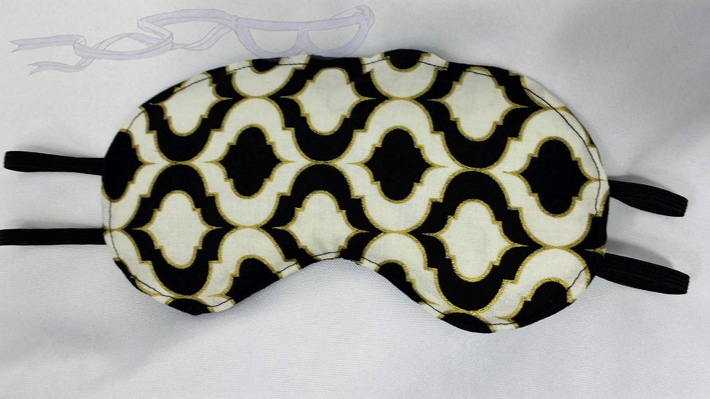 This sleep mask features a gold, black, and white repeating tiled pattern.
