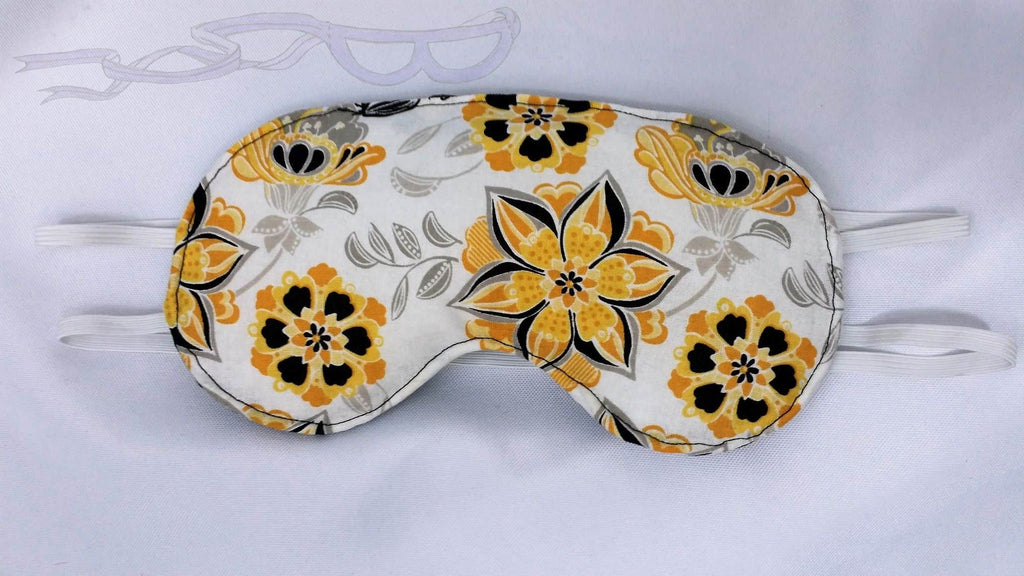 This sleep mask features yellow and black flowers on a white background.