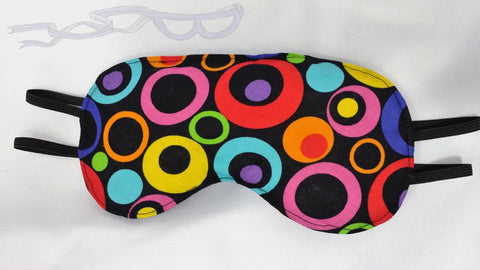 This sleep mask features brightly colored circles on a black background.