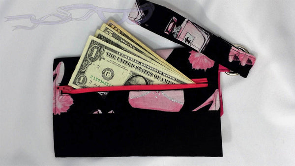 This small purse has pink puffy shoes and silver accented perfume bottles on a black background.