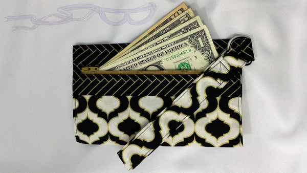 This small purse has gold bars on a black background matched with a geometric gold, black, and white design. It is handmade and one of a kind.