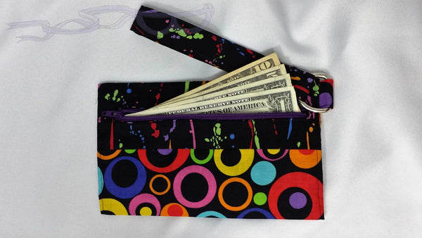 This small purse has colorful paint splatters on a black background matched with a colorful bunch off circles. It is handmade and one of a kind.