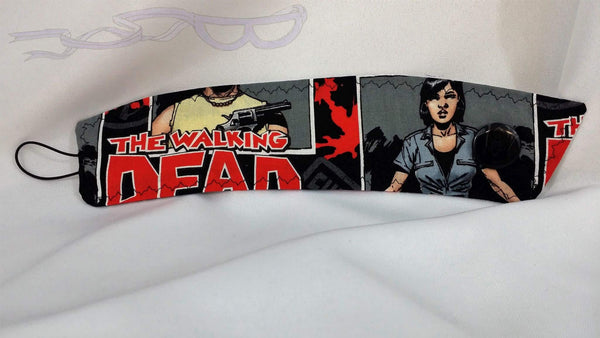 This coffee sleeve is made from The Walking Dead fabric. The design has a gray portrait box featuring Maggie from the comic book series on a black background with the logo.