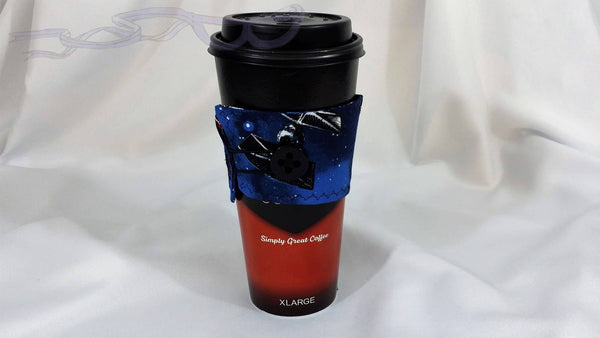 The cup cozy is made with cotton fabric on both sides and the inside has soft cotton for insulation. The closure is an elastic loop that goes around the button.