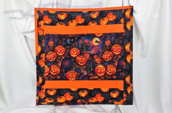 The design has pumpkins, a witch, witches hat, brooms, spider webs, eerie eyes, haunted house, and a full moon. The border has more pumpkins and webs with black spiders quilted into it.