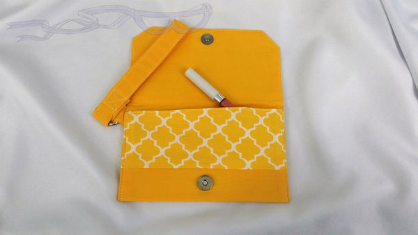 A lovely yellow tiled repeating pattern on a simple wristlet. This small purse has a geometric repeating design and cotton solid colored accent panels.