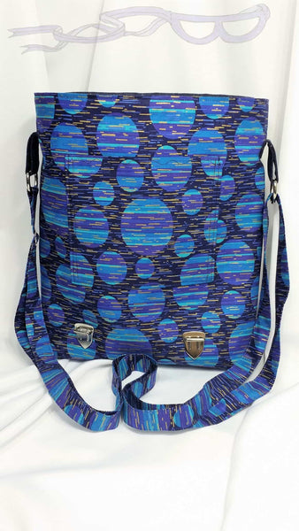 "This blue messenger bag is approximately 11"" x 12"" x 3"" (28 c x 30.5 cm x 7.6 cm). The front and back have outside pockets."