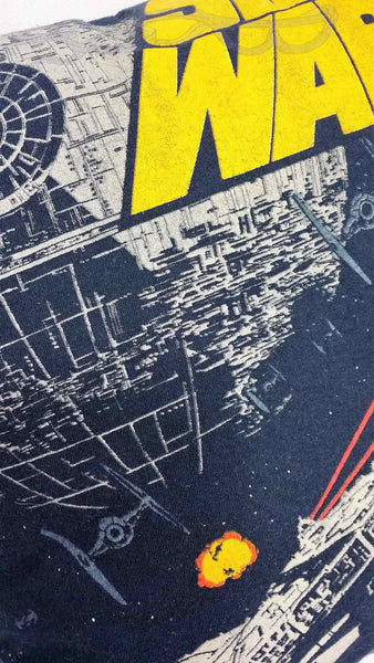 It features the Millennium Falcon and TIE fighters trading blows in front of the Death Star with the Star Wars logo in yellow, all on a navy background.