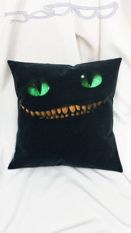 features the intense face the Cheshire Cat with green eyes, on a black background.  No Capes Store