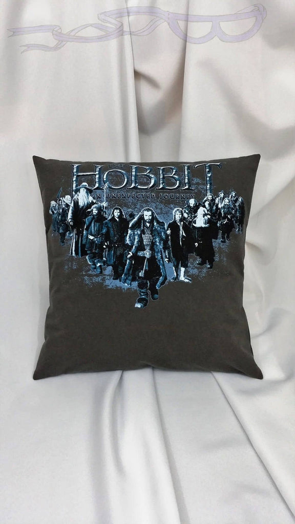 This unique movie pillow is made from a Lord of the Rings An Unexpected Journey movie tshirt. It features the whole group walking forward under the movie logo in blue tones on a dark beige background.