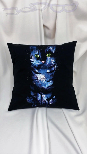 This cat pillow cover features a feline with green eyes, a pink nose, and the stars themselves make his fur in nebulous blues on a black background.