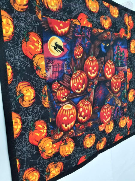 Halloween wall hanging with pumpkins, witches, and spider webs.