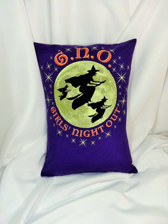 "This Girls' Night Out pillow cover features black silhouetted witches against a full moon on a purple background. It has stars and orange lettering stating, ""GNO Girls' Night Out""."