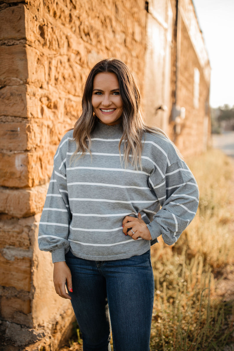 Striped pullover sweater with a mock neck.