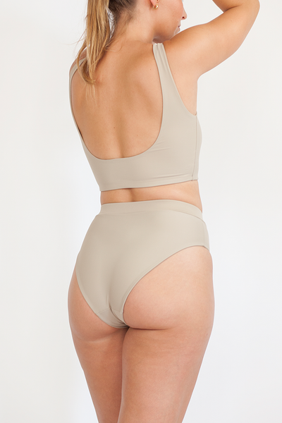 The back of a woman standing with her hands over head wearing high waisted full coverage nude bikini bottoms with a matching nude bikini top.