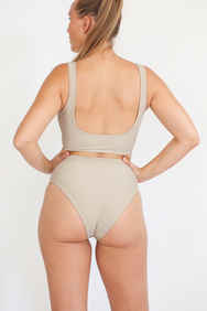 The back of a woman with her hands on her hips wearing a full coverage bikini in beige.
