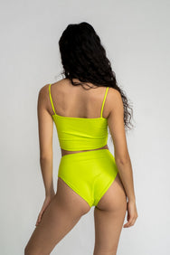The back of a woman standing wearing a bright neon green tankini top with matching bright green neon high waisted bikini bottoms.