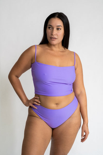 A woman standing with one hand on her hip looking to the side wearing high cut bright purple bikini bottoms with a matching bright purple tankini bikini top.