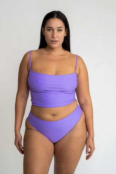 A woman standing with her arms by her side wearing bright lavender high-waisted bikini bottoms and a matching bright lavender tankini top.