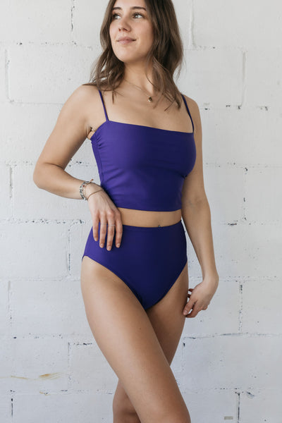 A woman standing with one hand on her hip and looking to the side wearing a dark purple tankini and matching dark purple high waisted bottoms.