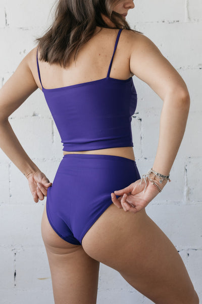 The back of a woman standing in front of a white wall wearing a dark purple tankini and dark purple high waisted bikini bottoms.