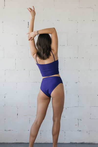 The back of a woman standing in front of a white wall with one arm in the air wearing a dark purple swimsuit with high waisted bikini bottoms and a tankini bikini top.