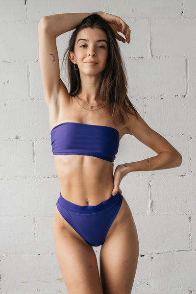 A woman standing with one hand on her hip and the other above her head wearing dark purple high waisted bikini bottoms with a matching dark purple strapless bandeau bikini top.
