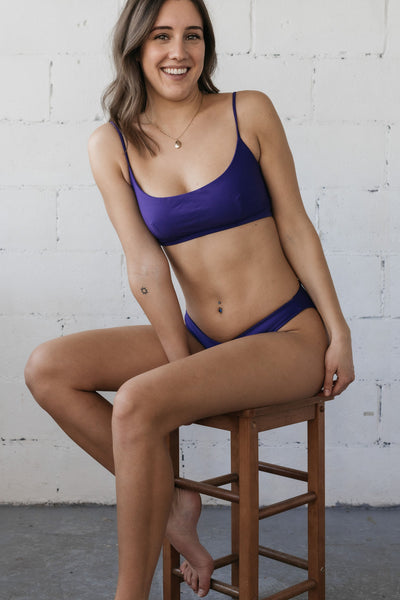 A woman sitting in a stool and smiling wearing dark purple v cut bikini bottoms with a matching dark purple scoop neck bikini top.
