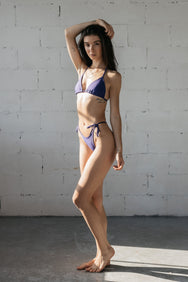 Woman standing with one leg bent in front of the other wearing dark purple triangle bikini bottoms with a matching dark purple adjustable triangle bikini top.