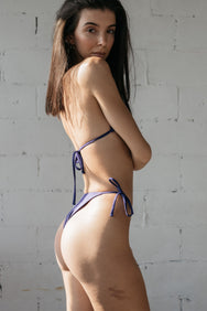 The back of a woman standing and looking over her shoulder wearing dark purple triangle bikini bottoms with a matching dark purple adjustable triangle bikini top.
