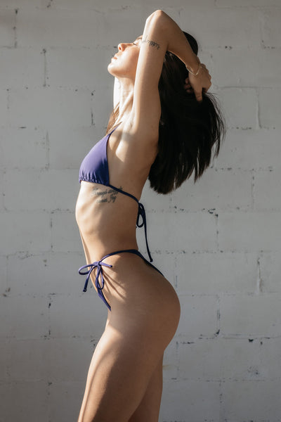 A woman standing to the side leaning back with her hands in her hair wearing dark purple string triangle bikini bottoms with a matching dark purple string triangle bikini top.