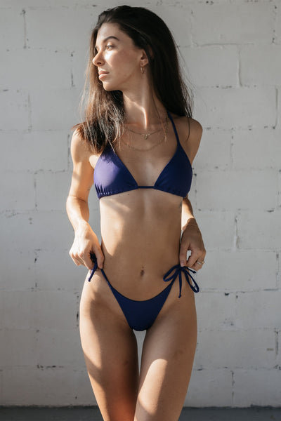 A woman standing with her hands holding her bikini bottoms wearing dark purple string triangle bikini bottoms with a matching dark purple string triangle bikini top.