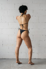 The back of a woman leaning to the side wrapping her arms around her wearing adjustable black triangle string bikini bottoms with a matching black triangle string bikini top.